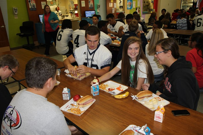 Warren Central High School football players visited Henry F. Moss Middle School to promote eating school lunch.