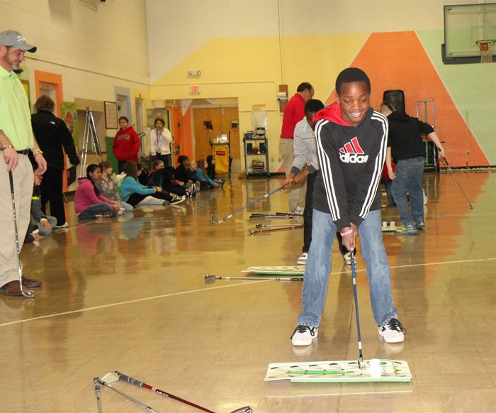 Golf pro Phil Jones and volunteer Sam Rzepka work with Warren Elementary School students on learning the sport of golf.