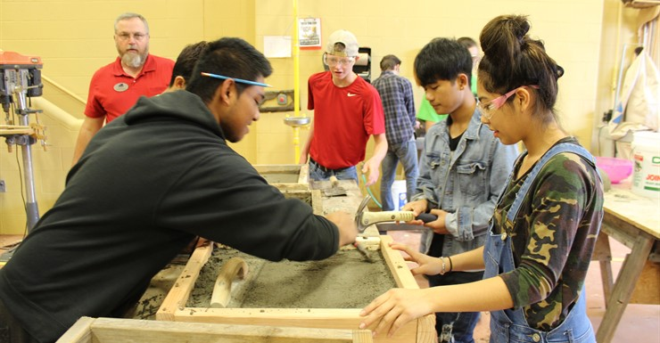 Construction students learn how to pour concrete to make pavers.